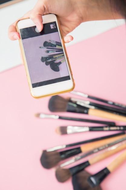 Sluit omhoog hand neem telefonisch een foto van make-upcosmetica en borstelsproducten op kleurrijke achtergrond Premium Foto