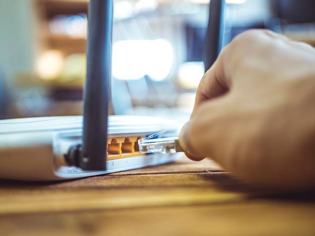 Sluit omhoog hand opnemend ethernet draad in wifi-router op houten lijst Premium Foto