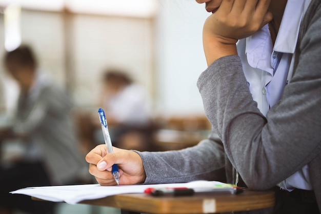 Sluit omhoog hand van studentenlezing en het schrijven examen met spanning in klaslokaal Premium Foto
