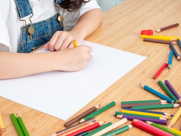 Sluit omhoog hand van weinig leuke tekening van het de kleurenpotlood van het meisjesgebruik bij witboek op houten lijst. Premium Foto