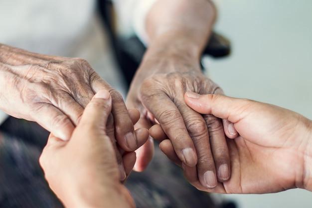 Sluit omhoog handen van het helpen van handen bejaarde thuiszorg. Premium Foto