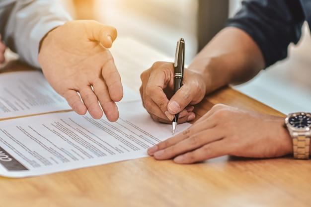 Sluit omhoog het contract van het de penteken van de handholding op document Premium Foto