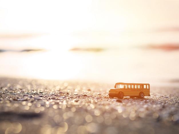 Sluit omhoog het gele stuk speelgoed van de schoolbus op zand bij zonsondergangstrand. Premium Foto