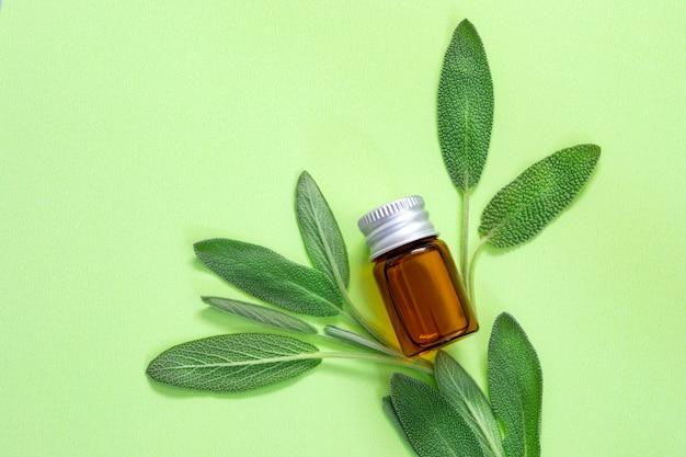 Sluit omhoog het verse groene wijze kruidblad met fles etherische olie op groene achtergrond Premium Foto