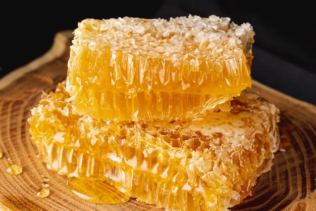 Sluit omhoog honingraten op houten schotel Gratis Foto