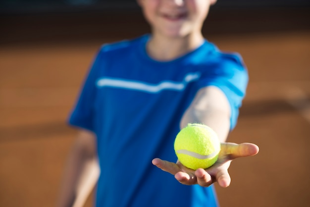 Sluit omhoog jong geitje die een tennisbal in hand houden Gratis Foto