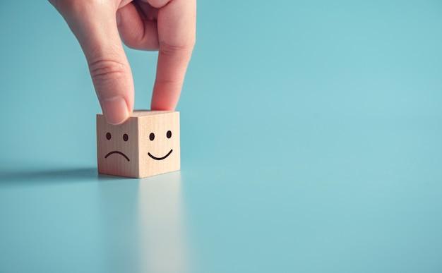 Sluit omhoog klantenhand kiezen smileygezicht en droevig gezichtspictogram op houten kubus Premium Foto