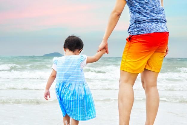 Sluit omhoog mamma hand in hand een kind op strand Premium Foto
