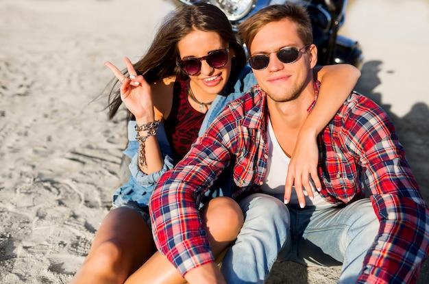 Sluit omhoog manierportret die van paarruiters op het zonnige strand stellen, dichtbij motor rusten, modieuze de zomeruitrusting, koele zonnebril dragen. romantische stemming. Gratis Foto