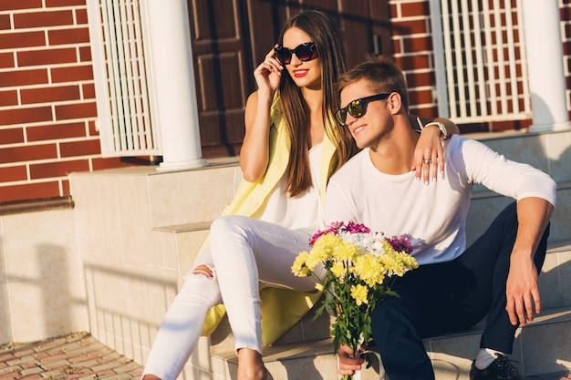 Sluit omhoog manierportret van jong modieus vrolijk paar in liefde stellen openlucht op straat, glimlachend, lachend, koesterend en samen genietend van tijd. heldere warme zonnige kleuren. romantische stemming. Gratis Foto