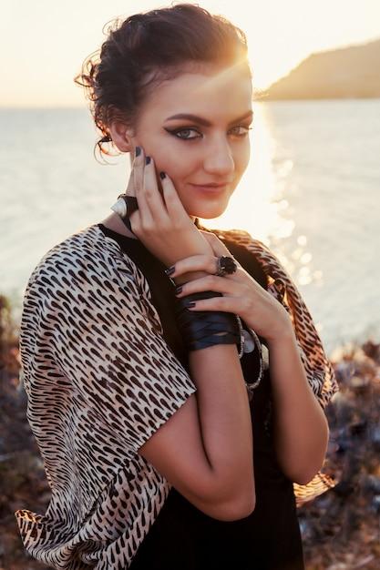 Sluit omhoog manierportret van mooie glimlachende vrouw bij zonneschijn. smokey eyes kijken. Gratis Foto