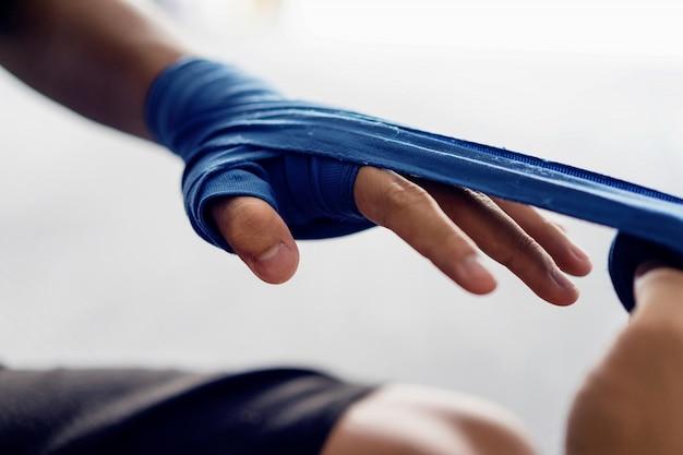 Sluit omhoog mannelijke hand van bokser met blauwe in dozen doende verbanden. Premium Foto