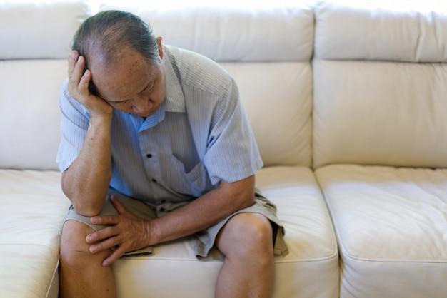Sluit omhoog mening van de aziatische hogere mens die aan hoofdpijn lijden. Premium Foto