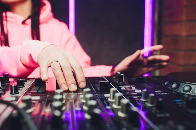 Sluit omhoog mening van de handen van mannelijke schijfjockey die muziek op zijn dek mengen met zijn handen klaar over het vinylverslag op de draaischijf en de controleschakelaars bij nacht. Premium Foto
