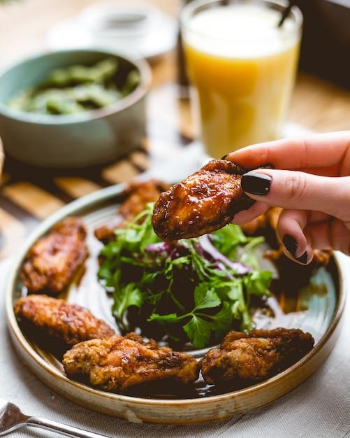 Sluit omhoog mening van een vrouwelijke hand die gebraden kippenvleugel houden Gratis Foto