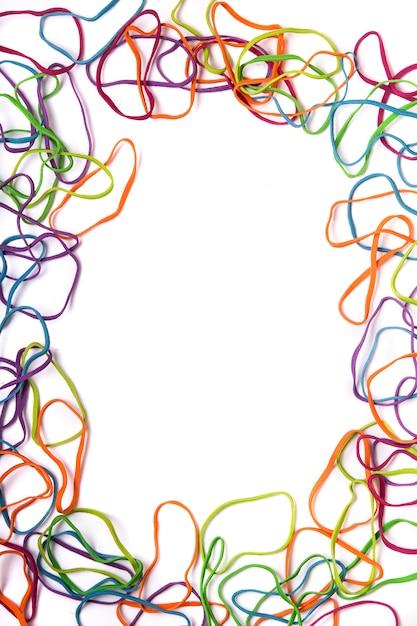 Sluit omhoog mening van verscheidene kleurrijke bureauelastiekjes die een rechthoek vormen die op een witte achtergrond wordt geïsoleerd. Premium Foto