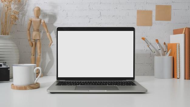 Sluit omhoog mening van werkplaats met lege het schermlaptop, houten cijfer, het schilderen borstel en koffiekop op wit bureau met bakstenen muur Premium Foto