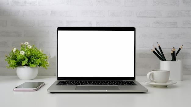 Sluit omhoog mening van werkruimte met lege het schermlaptop, telefoon, potloden, koffiekop en boompot op wit bureau met bakstenen muur Premium Foto
