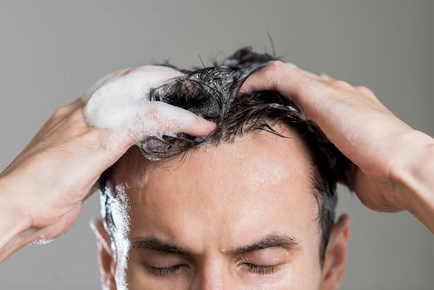 Sluit omhoog mens die zijn haar wast Gratis Foto