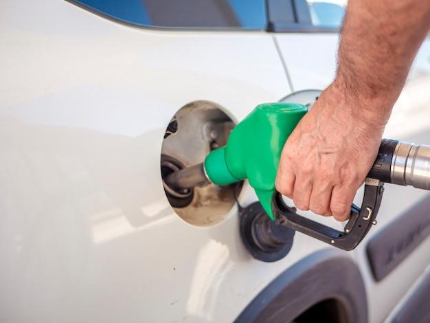 Sluit omhoog mensenhand die de witte auto vullen met brandstof Premium Foto