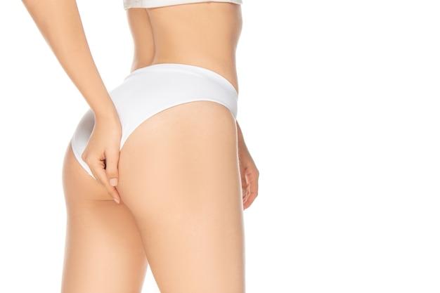 Sluit omhoog mooi vrouwelijk model dat op witte achtergrond wordt geïsoleerd. schoonheid, cosmetica, spa, ontharing, dieet en behandeling, fitnessconcept. fit en sportief, sensueel lichaam met een verzorgde huid. Gratis Foto