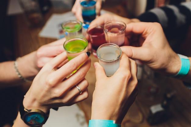 Sluit omhoog ontsproten van groep mensen die glazen met wijn of champagne clinking Premium Foto