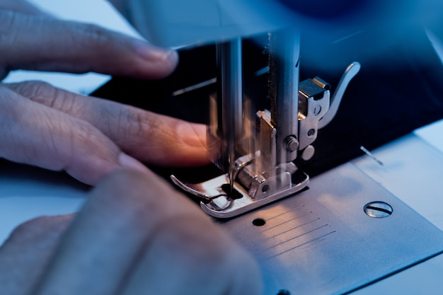 Sluit omhoog op naaimachine met handen het werken Premium Foto