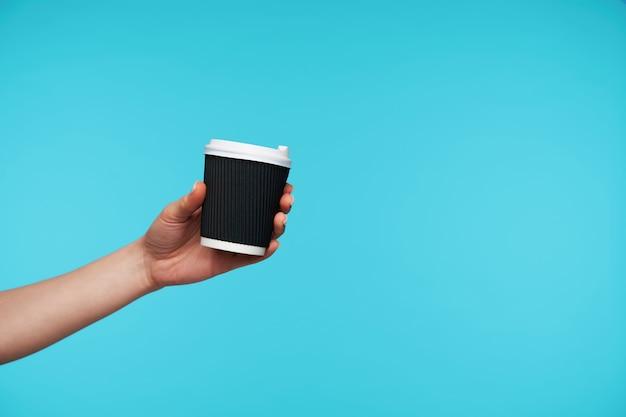 Sluit omhoog op zwarte document kop met koffie die met de hand wordt gehouden Gratis Foto
