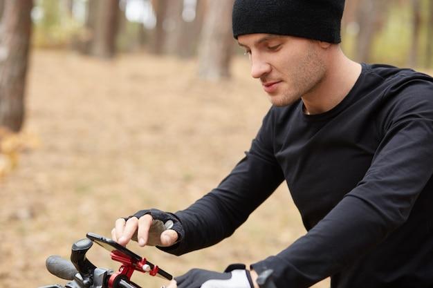 Sluit omhoog openluchtportret van jonge mannelijke fietser gebruikend mobiele telefoon op straat Premium Foto