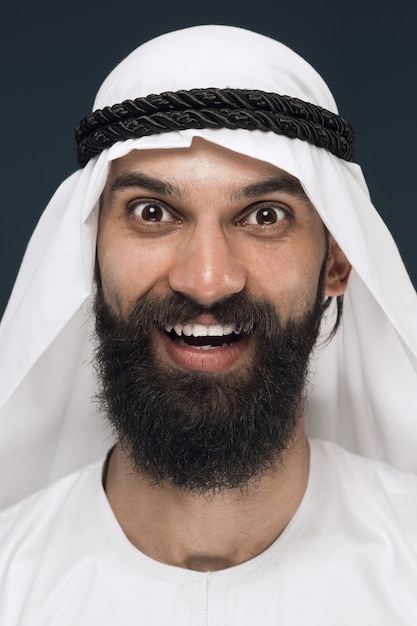 Sluit omhoog portret van arabische saoedische zakenman op donkerblauwe studioachtergrond. jonge mannelijke model staan en glimlachen, ziet er gelukkig uit. concept van zaken, financiën, gezichtsuitdrukking, menselijke emoties. Gratis Foto
