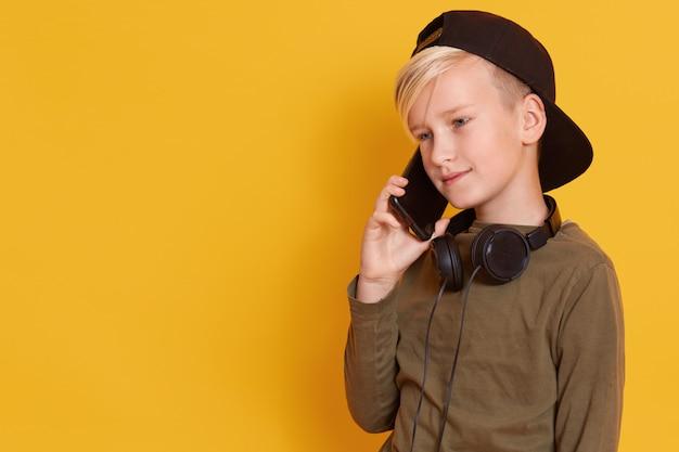 Sluit omhoog portret van blondejongen die door mobiele telefoon spreken en prettige gelaatsuitdrukking hebben, het charmante model stellen geïsoleerd op geel. kopieer ruimte voor reclame of promotie. Premium Foto
