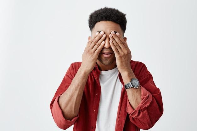 Sluit omhoog portret van de donkerhuidige ogen van de mensenkleding met handen, proberend om te ontspannen na het lange werken met laptop computer in bureau. man met hoofdpijn en moe. Gratis Foto