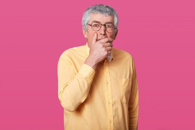 Sluit omhoog portret van de mens met zwarte ronde glazen, gekleed geel overhemd en vlinderdas. bejaarde senior met wijd open ogen, heeft geschokte gezichtsuitdrukking, ergens bang voor, met mond met hand. Gratis Foto