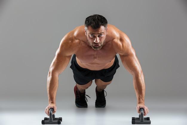 Sluit omhoog portret van een ernstige sterke shirtless mannelijke bodybuilder Gratis Foto