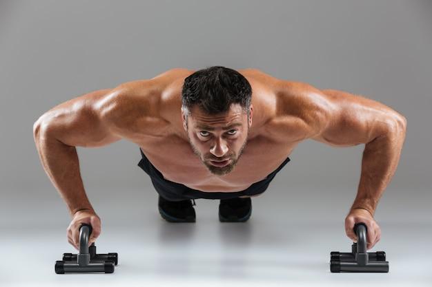 Sluit omhoog portret van een zekere sterke shirtless mannelijke bodybuilder Gratis Foto