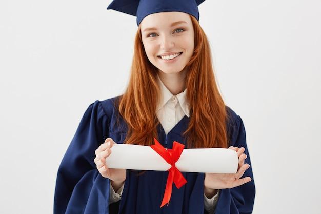 Sluit omhoog portret van gelukkige foxyvrouwengediplomeerde in glb-het glimlachen holdingsdiploma. jonge redhead studente toekomstige advocaat of ingenieur. Gratis Foto