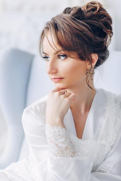 Sluit omhoog portret van jonge mooie bruid in elegante witte robezitting op een stoel in een helder binnenland Premium Foto