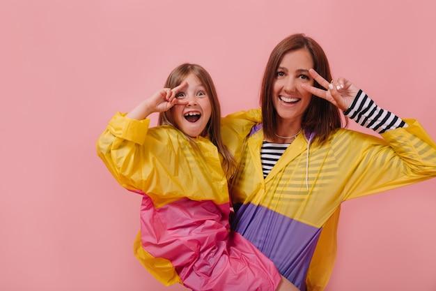Sluit omhoog portret van mooie vrouw die heldere regenjas draagt die haar charmante dochtertje houdt en vredesteken toont Gratis Foto