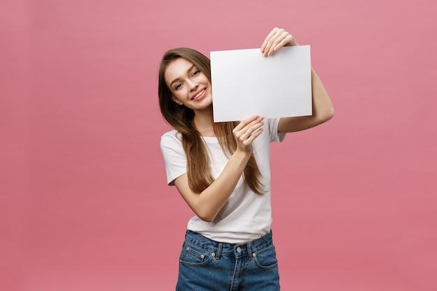 Sluit omhoog portret van positieve lachende vrouw die en witte grote modelaffiche glimlachen houden Premium Foto