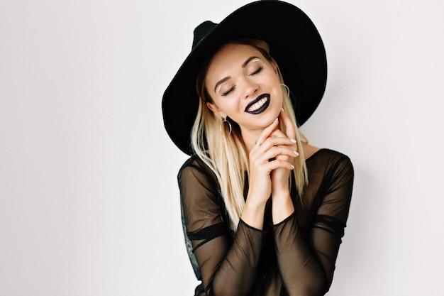 Sluit omhoog portret van romantische mooie vrouw met donkere lippen die over geïsoleerde muur stellen met gelukkige glimlach en gesloten ogen die zwarte hoed dragen Gratis Foto