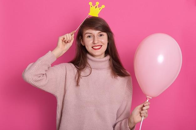 Sluit omhoog portret van schitterende trendy jonge vrouw in partijuitrusting en verjaardagskroon Premium Foto