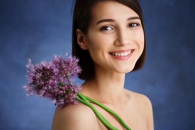 Sluit omhoog portret van tedere jonge vrouw met lilac bloem over blauwe muur Gratis Foto