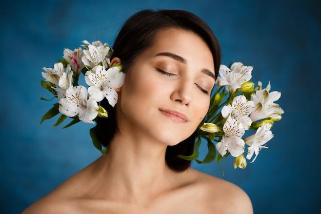 Sluit omhoog portret van tedere jonge vrouw met witte bloemen over blauwe muur Gratis Foto