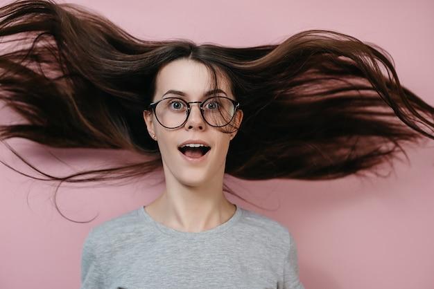 Sluit omhoog portret van verraste vrouw in glazen met vliegend haar en wijd open mond. Premium Foto