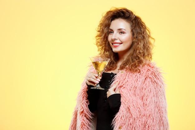 Sluit omhoog portret van vrolijk glimlachend mooi donkerbruin krullend meisje in roze de cocktailglas van de bontjasholding over gele muur Gratis Foto