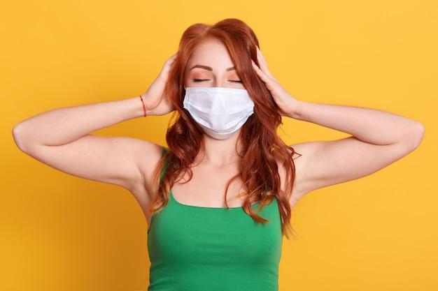 Sluit omhoog portret van vrouw die medisch masker en groen t-shirt dragen, haar hoofd aanraken, geïsoleerd stellen, met hoofdpijn Premium Foto