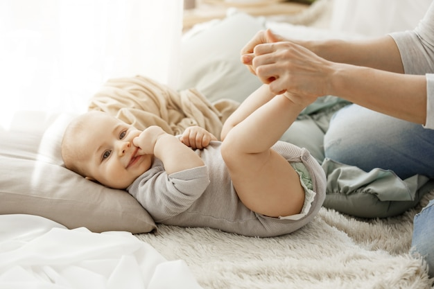 Sluit omhoog portret van weinig pasgeboren zoon liggend op bed, terwijl het spelen met moeder. het jonge geitje glimlachen en legde zijn vingers gelukkig en onbezorgd in lookin mond. Gratis Foto