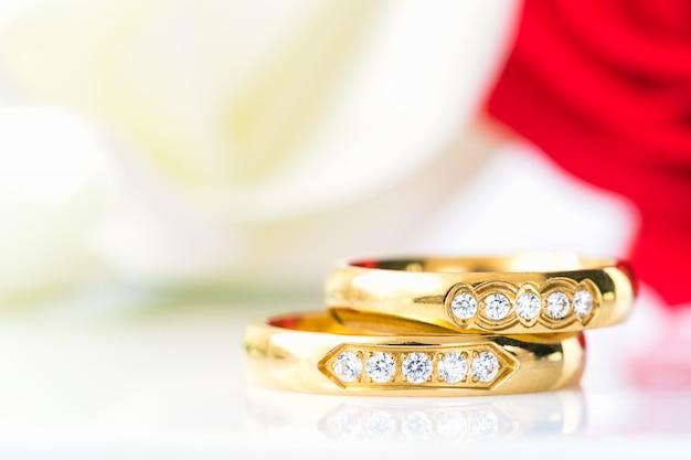 Sluit omhoog rode rozen en gouden ringen op wit Premium Foto