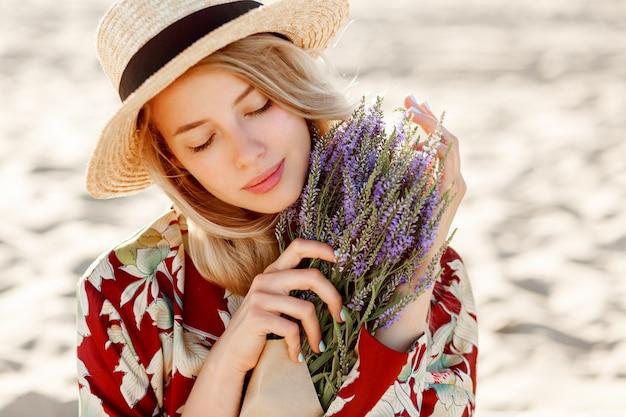 Sluit omhoog schoonheidsportret van mooi romantisch blond meisje die van perfecte geur van lavendel genieten. huidverzorging en cosmetisch concept. warme zonsondergangkleuren. sluit de ogen. Gratis Foto