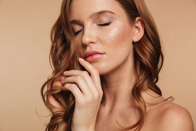 Sluit omhoog schoonheidsportret van sensuele gembervrouw met het lange haar stellen met gesloten ogen Gratis Foto